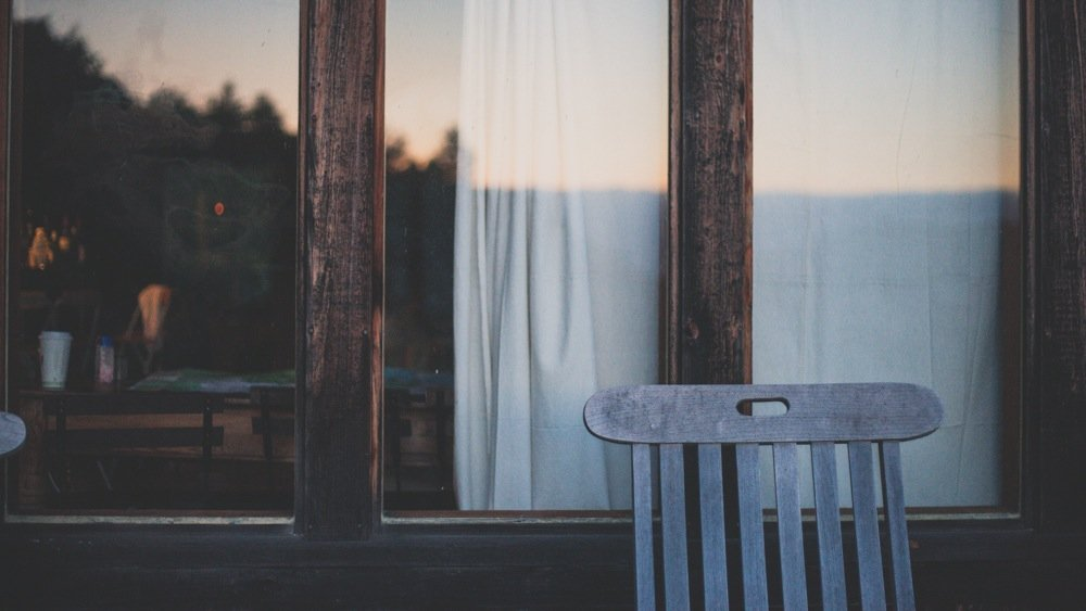 Empty chair on a porch featuring an article written about suicide.